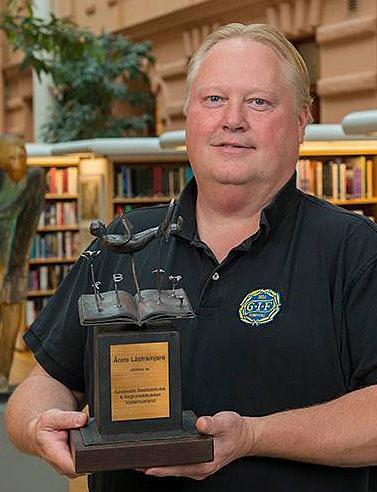 Tomas Jonsson står och håller i priset för Årets läsfrämjare